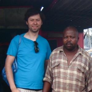 Manuel Marindze und ich vor seinem Imbissstand auf dem Markt von Xipamanine in Maputo, wo seine Frau und er Broiler mit Pommes verkaufen